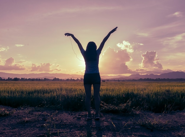 Free happy woman raising arms watching the sun