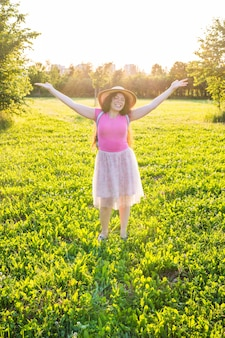 일출 배경에서 태양을 바라보며 팔을 들고 있는 무료 행복한 젊은 여성.