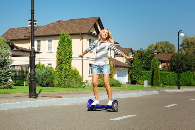 새처럼 자유롭게. 자가 균형 스쿠터를 타고 거리를 따라 손을 펴고 신선한 공기를 즐기는 즐거운 젊은 여성