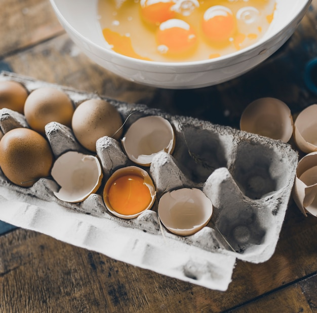 Free range eggs cracked in a egg carton with a bowl at the background.