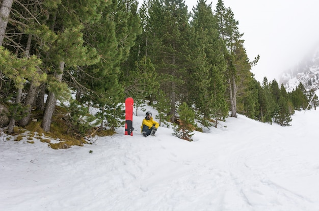 Free rider with snowshoes and snowboard on his back.