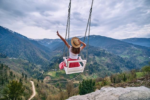하늘의 스윙과 마운틴 뷰에서 스윙을 즐기는 두 팔을 벌려 무료 로맨틱 한 여성 여행자. 사람이 행복을 느끼고 삶과 자유를 느끼는 조용하고 조용한 방랑벽 컨셉의 순간