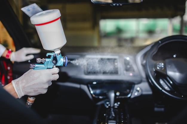 車にcovid-19ウイルスを注入するための無料サービス。保護マスクを着用し、車にcovid-19消毒剤をスプレーする整備士の写真。