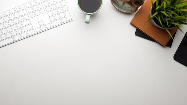 Свободное место в учебном столе белый стол с клавиатурой пк кофейная кружка белый фон вид сверху