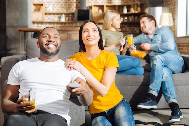 Свободное время. энергичная восторженная милая пара сидит вместе, глядя вверх и просматривая фильм