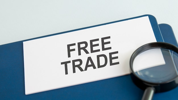 Free trade word on white paper card and magnifying lens