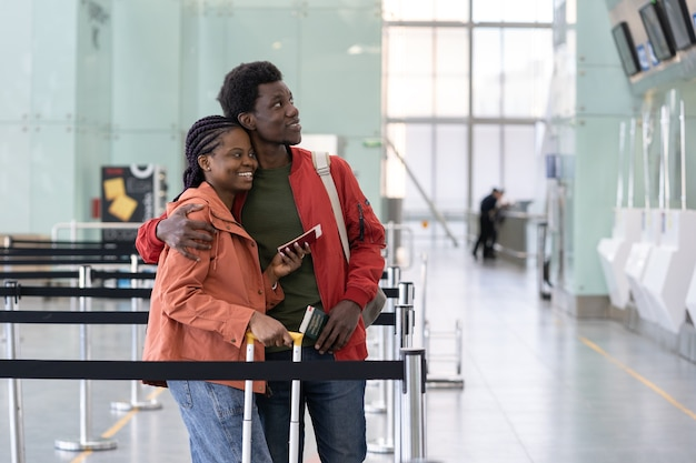 Free to travel african couple wait for checkin for flight at the airport