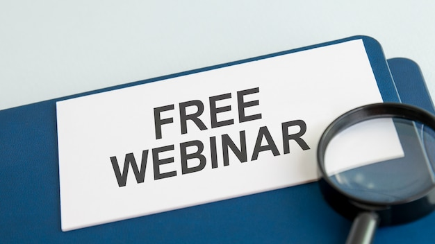 Free webinar word on white paper card and magnifying lens