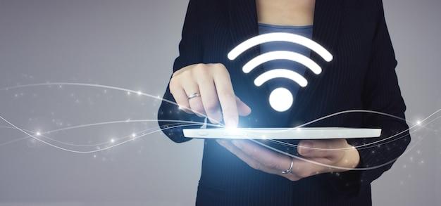 Концепция интернет технологии сигнала беспроводной сети wi-fi. белая таблетка в руке коммерсантки с цифровым знаком wi-fi голограммы на серой предпосылке. бизнес-концепция сетевого подключения.