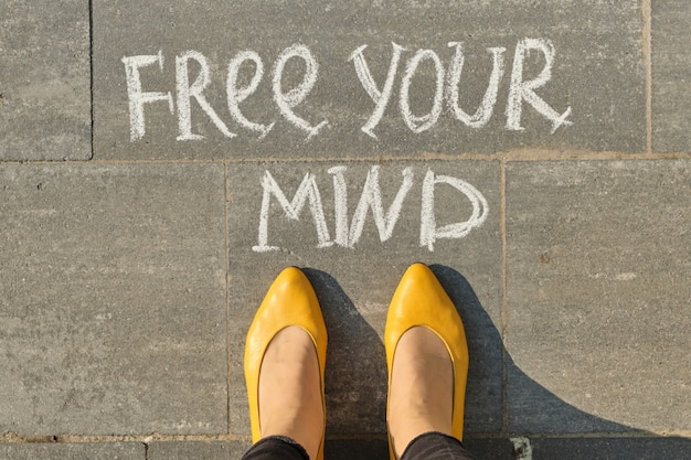Free your mind text on gray sidewalk with woman legs, top view