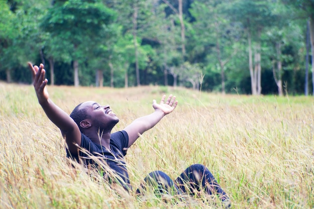Freedom african man enjoying nature on grass meadow