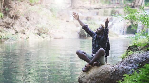 森と滝の背景にバックパックと帽子で自由アフリカ人旅行冒険。旅行のコンセプト