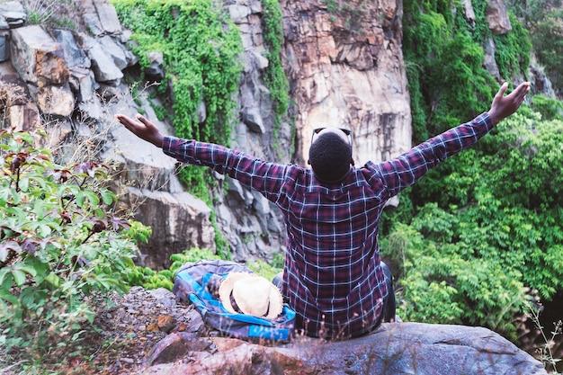 バックパックと帽子で山の上に座っている自由アフリカ旅行者