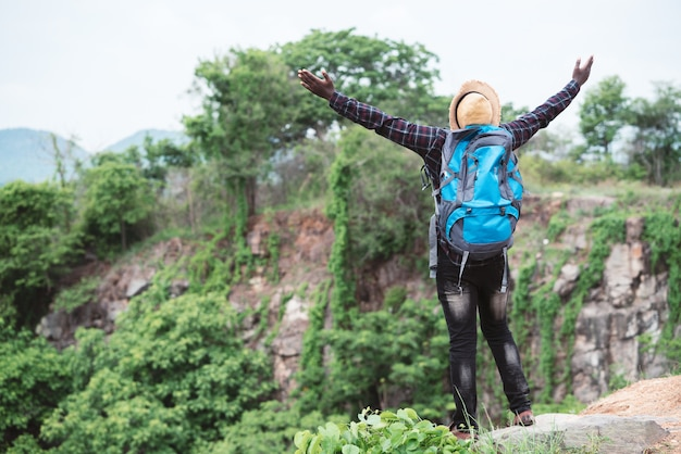 Freedom african traveler  sitting on top of the mountain with backpack and hat