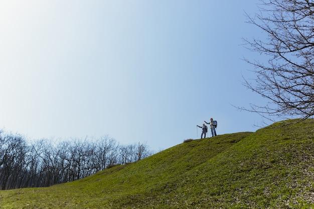 항상 자유. 화창한 날에 나무 근처 녹색 잔디밭에서 산책하는 관광 복장에 남녀의 세 가족 커플. 관광, 건강한 라이프 스타일, 휴식 및 공생의 개념.