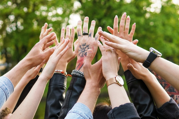 自由と友情。空中に手を上げている若者のグループ。