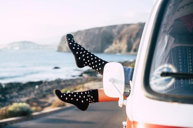 海岸近くに駐車された古典的なバンの窓から女性の足のペアで自由と幸福のコンセプトイメージ。オルタナティブでポジティブなライフスタイルのためのオーシャンビュー。旅行して世界を楽しむ、ea