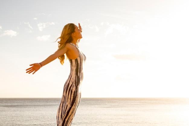 自由と喜びの概念の人々は、立って陽気な美しい若い白人女性が腕を開き、屋外のnaureレジャー活動を楽しんで幸せなライフスタイル-海の背景と空