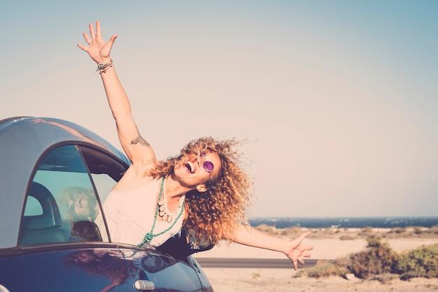 Свобода и путешествия счастливые смеющиеся люди концепция с красивой кавказской молодой женщиной из машины, наслаждаясь местом назначения, открывая руки и крича бесплатно