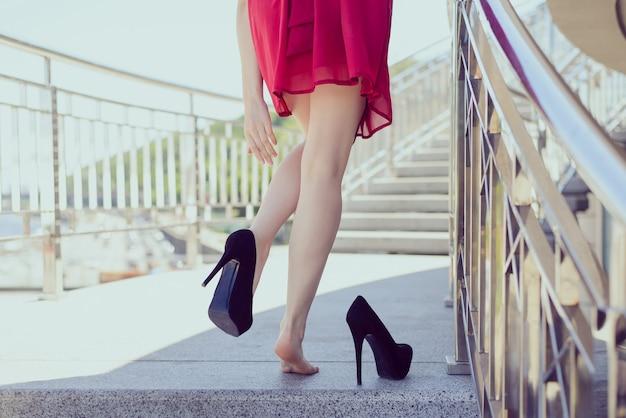 나이트 클럽 마사지 후 프리덤 클래식 드레스 코드 아침 일출은 지친 소녀 컨셉을 착용합니다. 불편한 검은 신발을 벗는 엉덩이 엉덩이 손의 클로즈업 사진 뒤에서 읽기