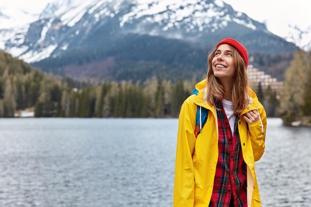 自由の概念。空に焦点を当てた美しいのんきな女性観光客は、山岳リゾートでの休暇を楽しんでいます