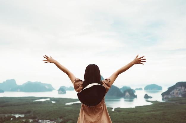 自由の概念。自由な時間を楽しんで、自然の川や山で手を開いて幸せな若い女性