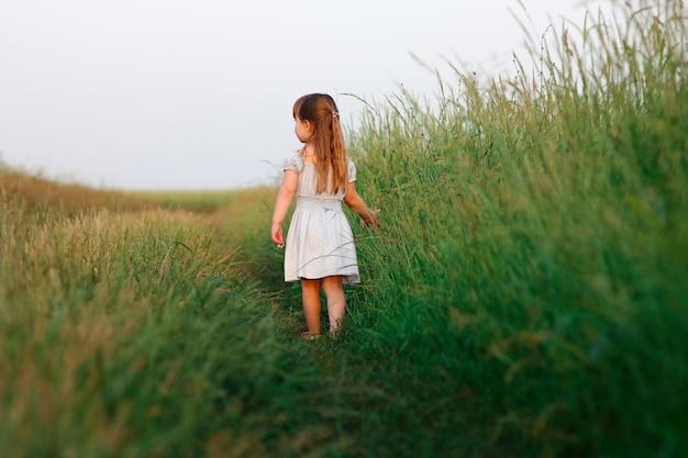 緑のフィールドの近くの自由の概念の小さな幸せな女の子