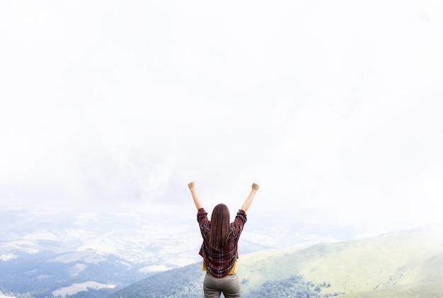 自由の概念。景色を楽しみながら山の頂上に立って手を上げている女性