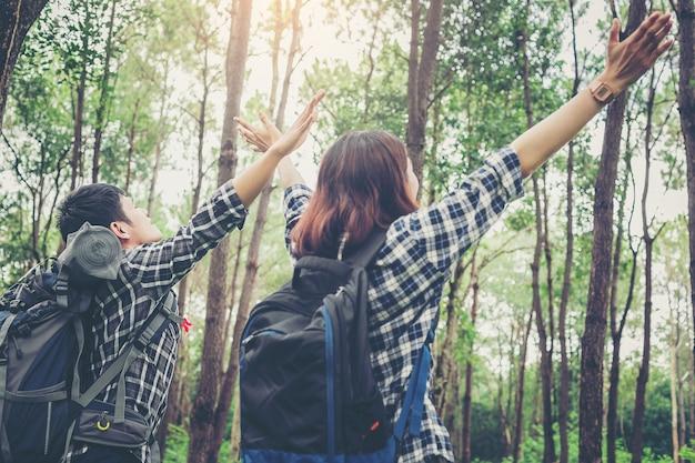 배낭이 열리는 팔을 가진 자유 커플 등산객은 큰 숲에서 자연을 즐길 수 있습니다.