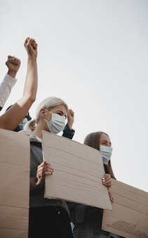 Freedom. group of activists giving slogans in a rally. caucasian men and women marching together in a protest in the city. look angry, hopeful, confident. blank banners for your design or ad.