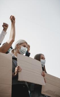 자유. 집회에서 구호를 외치는 활동가 그룹. 백인 남성과 여성이 도시에서 함께 행진하고 있다. 화난 표정, 희망적이고 자신감 있는 표정. 디자인 또는 광고를 위한 빈 배너입니다.