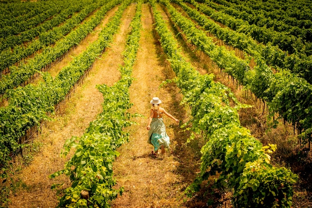 Freedom and happiness people concept enjoying nature - woman viewed from back running free in vineyard nature outdoor - travel and joyful lifestyle concept - trendy fashion style lady enjoy country