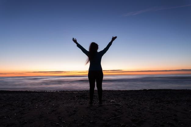 自由、休日、勝利の概念-日没時に海のビーチに立っているときに手を上げて女性のシルエット。