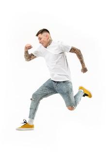 움직이는 자유. 점프 하 고 흰색 스튜디오에 대 한 몸짓 잘 생긴 행복 한 젊은 남자의 공중 샷