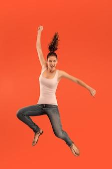 移動の自由。オレンジ色のスタジオの背景にジャンプして身振りで示すかなり幸せな若い女性の空中ショット。人間の感情と表情の概念