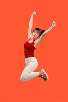移動の自由。オレンジ色のスタジオの背景にジャンプして身振りで示すかなり幸せな若い女性の空中ショット。動いているまたは動いているrunninの女の子。人間の感情と表情の概念