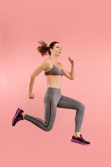 移動の自由。オレンジ色のスタジオの背景に対してジャンプして身振りで示すかなり幸せな若い女性の空中ショット。動いているまたは動いているrunninの女の子。人間の感情と顔の表情の概念 無料写真