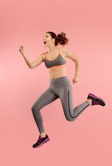 移動の自由。オレンジ色のスタジオの背景にジャンプして身振りで示すかなり幸せな若い女性の空中ショット。動いているまたは動いているrunninの女の子