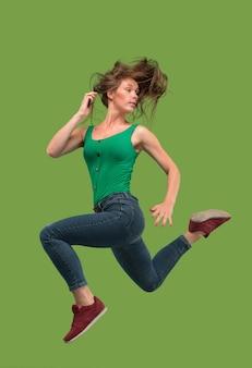 移動の自由。オレンジ色のスタジオの背景にジャンプして身振りで示すかなり幸せな若い女性の空中ショット。動きや動きで走っている女の子。
