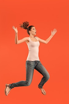 移動の自由。オレンジ色のスタジオの背景に対してジャンプして身振りで示すかなり幸せな若い女性の空中ショット。