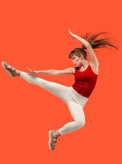 움직이는 자유. 점프 하 고 오렌지 스튜디오에 대 한 몸짓 꽤 행복 한 젊은 여자의 공중 샷.