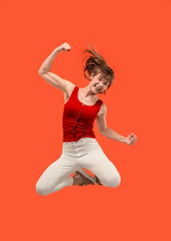移動の自由。オレンジに対してジャンプして身振りで示すかなり幸せな若い女性の空中ショット