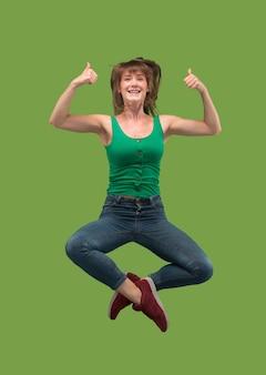 移動の自由。緑の上でジャンプして身振りで示すかなり幸せな若い女性の空中ショット