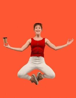 움직이는 자유. 오렌지 배경 점프 예쁜 젊은 여자