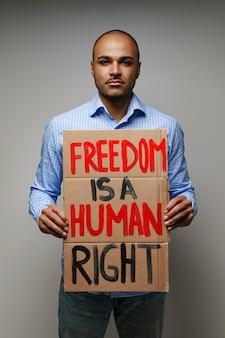 抗議者の手にある「自由は人権である」プラカード