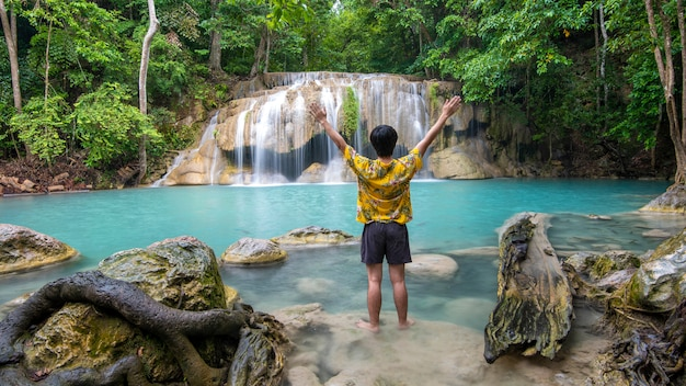A freedom man is enjoying with beautiful waterfall in tropical forest