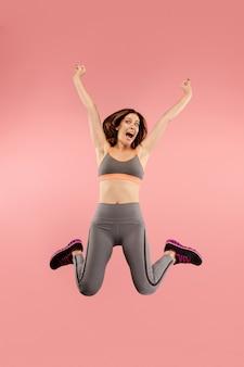 Libertà di movimento. colpo a mezz'aria di giovane donna abbastanza felice che salta e che gesturing contro il fondo arancio dello studio. ragazza che corre in movimento o in movimento. le emozioni umane e il concetto di espressioni facciali