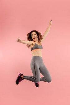 Libertà di movimento. colpo a mezz'aria di giovane donna abbastanza felice che salta e che gesticola contro il fondo arancio dello studio. ragazza in esecuzione in movimento o movimento. le emozioni umane e il concetto di espressioni facciali