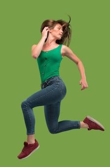 Libertà di movimento. colpo a mezz'aria di giovane donna abbastanza felice che salta e che gesturing contro lo studio arancione.