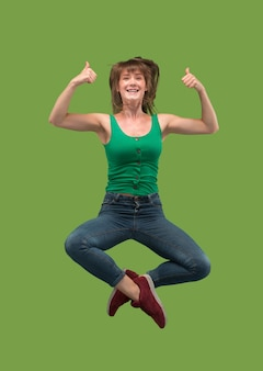 Libertà di movimento. colpo a mezz'aria di giovane donna abbastanza felice che salta e che gesticola sul verde